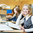 Smiling young adult woman reading book in library — Stock Photo #8731519
