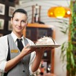 Waitress girl with cake on plate at restaurant — Stockfoto