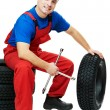 Automobile mechanic with car tire and spanner — Stock Photo #8732550