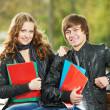 Two smiling young students studying outdoors — Stock Photo #8732780