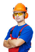 Builder in hard hat, earmuffs and goggles — Stock Photo