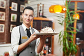 Waitress girl with cake on plate at restaurant — Stock Photo
