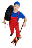 Automobile repairman with tire and lifting jack — Stock Photo