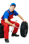 Automobile mechanic with car tire and spanner — Stock Photo