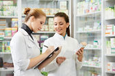 Pharmacy chemist women in drugstore — Stock Photo