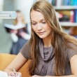 Young student girl working with book in library - Stockfoto