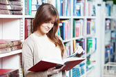 Young student girl reading book in library — Stock Photo