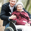 Old senior woman in wheelchair with careful son — Stock Photo #8810802