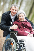 Old senior woman in wheelchair with careful son — Stock Photo
