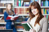 Young student girl study with book in library — Stock Photo