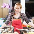 Smiling woman cooking in her kitchen — Stock Photo