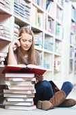 Smiling young adult woman reading book in library — Stock Photo
