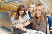 Young student girls working with laptop in library — Stock Photo