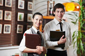 Waitress girl and waiter man in restaurant — Photo