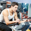 Positive man at legs bicycle exercises machine — Foto de Stock