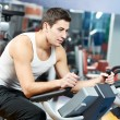 Positive man at legs bicycle exercises machine — 图库照片