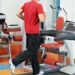 Positive man at legs exercises machine — Stock Photo
