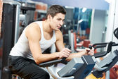 Positive man at legs bicycle exercises machine — Stock Photo