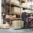 Worker driver at warehouse forklift loader works — Stock Photo