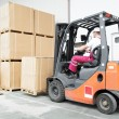 Worker driver at warehouse forklift loader works — Stock fotografie