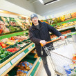 Man choosing vegetables in supermarket store - Stock Photo