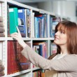 Stock Photo: Young adult student selecting book in library