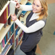 Stock Photo: Young adult student choosing book in library