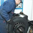 Machanic repairmat tyre balancing adjustment — Stock Photo #9171477
