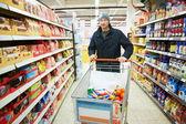 Man choosing vegetables in supermarket store — Stock Photo