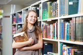 Young student girl with books in library — Stock Photo