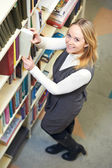 Young adult student choosing book in library — Stock Photo
