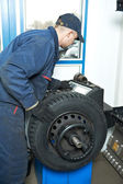 Machanic repairman at tyre balancing adjustment — Stock Photo