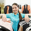 Woman seller consultant in clothes shopping store - Stock Photo