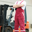 Warehouse worker in front of forklift — Stock Photo