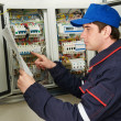 Electrician at work with draw plan — Stock Photo