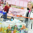 Woman at supermarket dairy shopping - Stock Photo