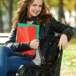 Student Girl sitting on bench outdoors - Stock Photo
