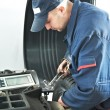 Stock Photo: Machanic repairman at tyre balancing adjustment