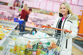 Woman at supermarket dairy shopping — Stock Photo