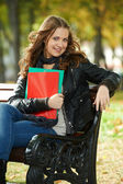 Student Girl sitting on bench outdoors — Stock Photo