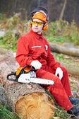дровосек работника с бензопилой в лесу — Стоковое фото