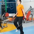 Positive man at legs exercises with skipping rope — Stock Photo #9539371