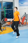 Positive man at legs exercises with skipping rope — Stock Photo