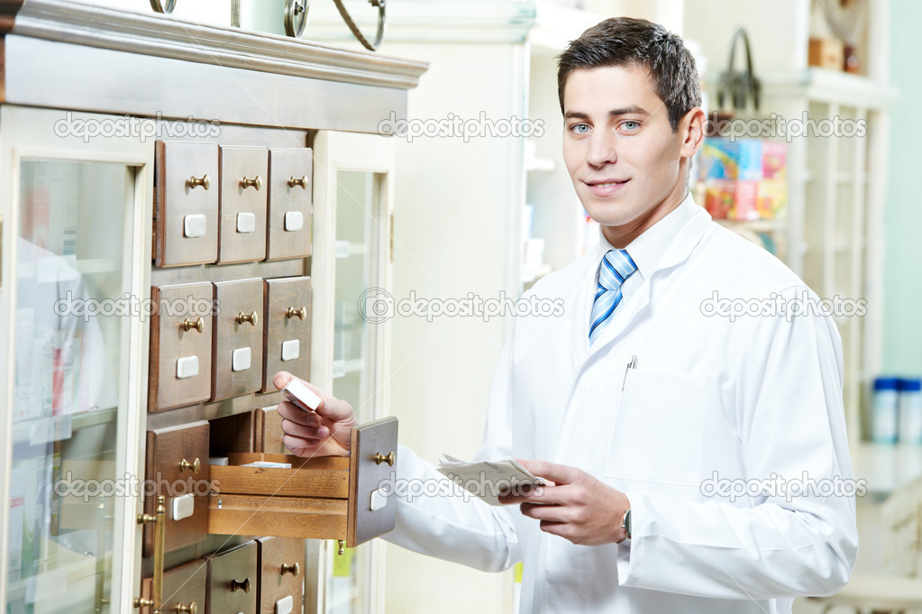 Young pharmacist chemist man working in pharmacy drugstore with prescription — Stock Photo #9539266