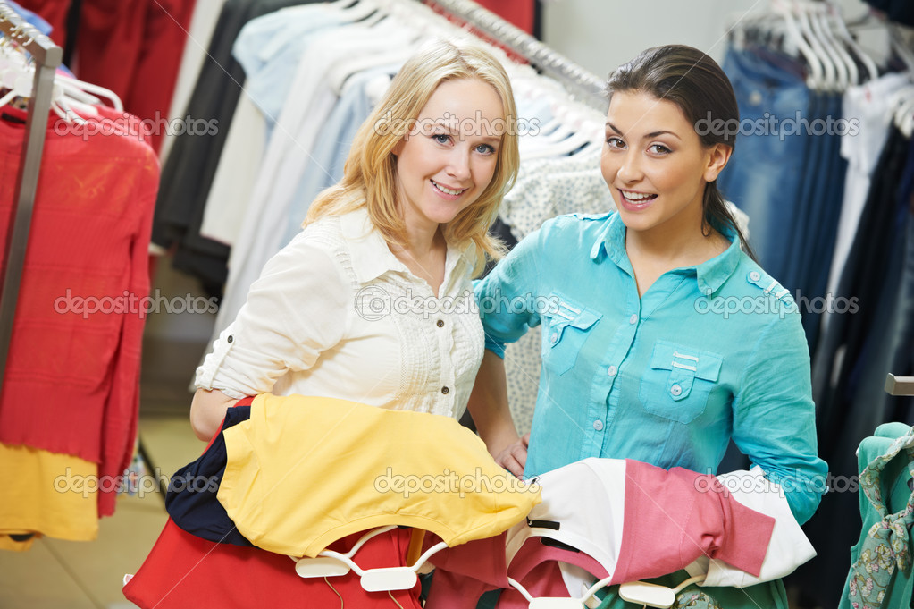 Two Young women with apparel shirt or blouse during garments clothing shopping at store — Stock Photo #9539530