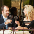 Man and girl with wine at cafe on a date - Stock Photo
