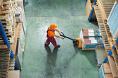 Worker with fork pallet truck — Photo