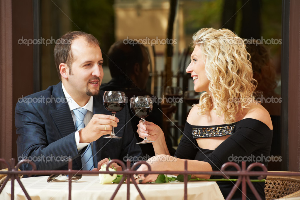 Man and girl drinking wine at street cafe on a date with flower on table — Stock fotografie #9696468