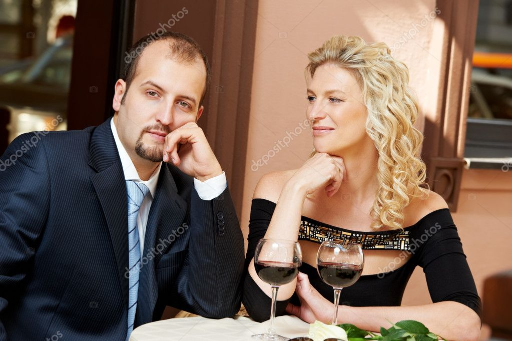 Man and girl drinking wine at street cafe on a date with flower on table — Stock Photo #9696482