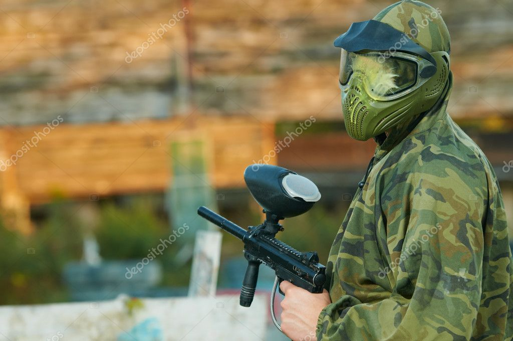 Happy paintball sport player man in protective camouflage uniform and mask with marker gun outdoors — Stock Photo #9697076